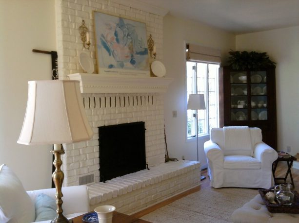 eclectic living room with white brick fireplace with mantel shelf and white wall