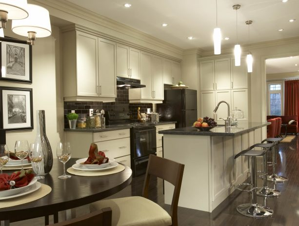 traditional open kitchen with antique white recessed style cabinets and black appliances
