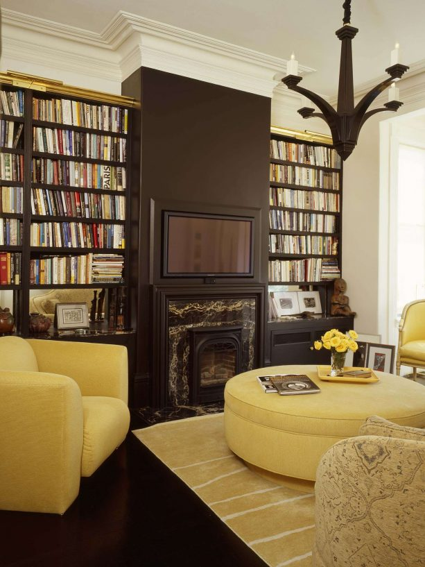 modern library living room with chocolate brown bookshelves and fireplace with blonde yellow sofa color ideas