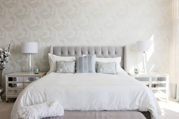 a grey and white bedroom with white mirrored bedside tables