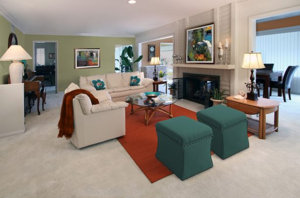 a living room with teal ottomans and rust rug
