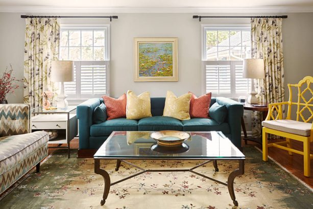 grey and teal living room with rust and yellow pillows