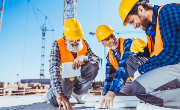 three construction workers review plans while discussing common construction injuries