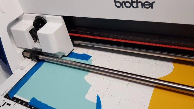 Using masking or painters tape to firmly hold the cardstock down on the Scan N Cut mat