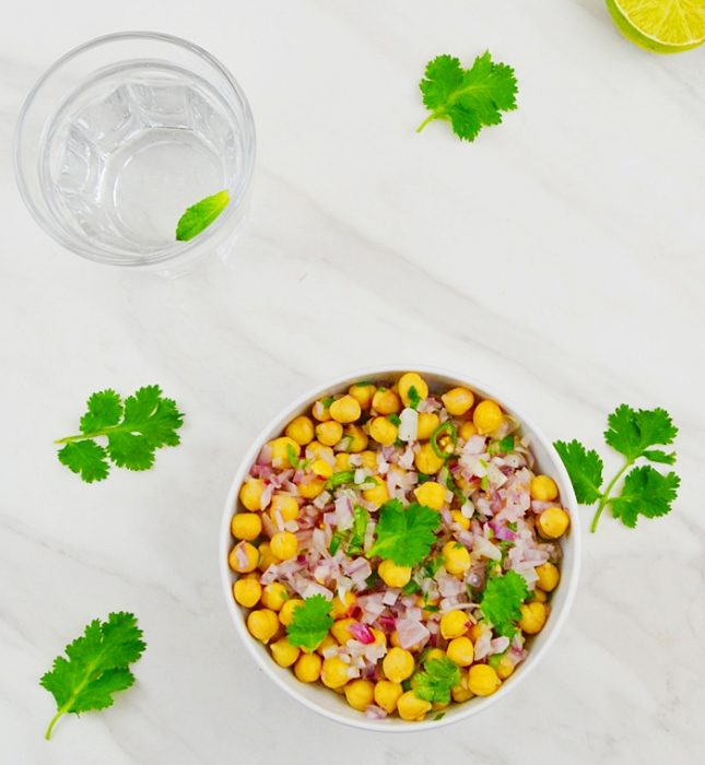 simple chickpea salad in a white bowl with glass of water