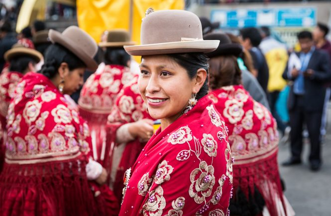 Bolivian girl wearing red shawl and bowler hat