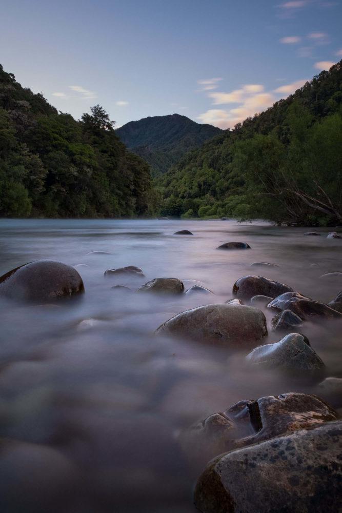 Langzeitbelichtung eines Flusses mit Steinen und Wald im Hintergrund