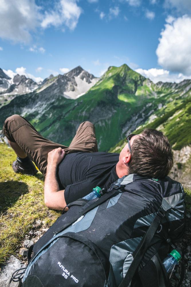 Wanderer liegt auf seinem Rucksack vor einer Bergkulisse