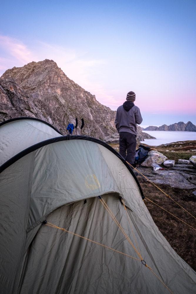 Wanderer steht vor Zelt und blickt auf die Berge