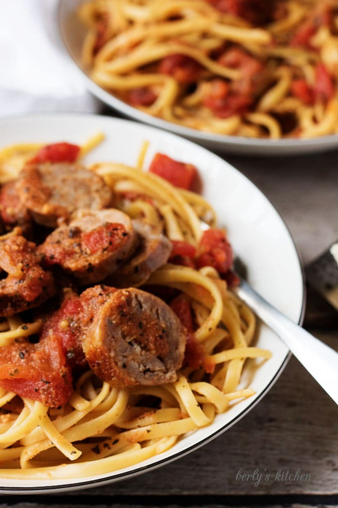 Close up of pasta, sausage, and tomato sauce with a fork.