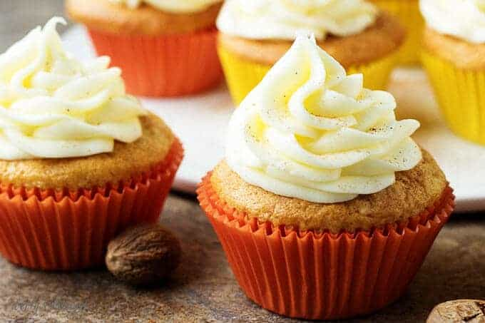 A close-up view of the finished eggnog cupcakes with buttercream frosting in red liners.