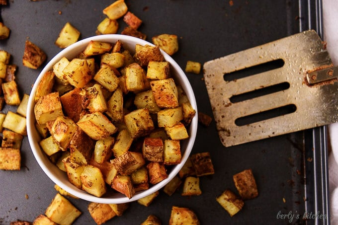 Top-down view of the home fries recipe in bowl, on a sheet pan with a spatula.