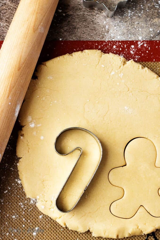 The rolled out dough being cut into fun holiday shapes like candy canes and ginger men.