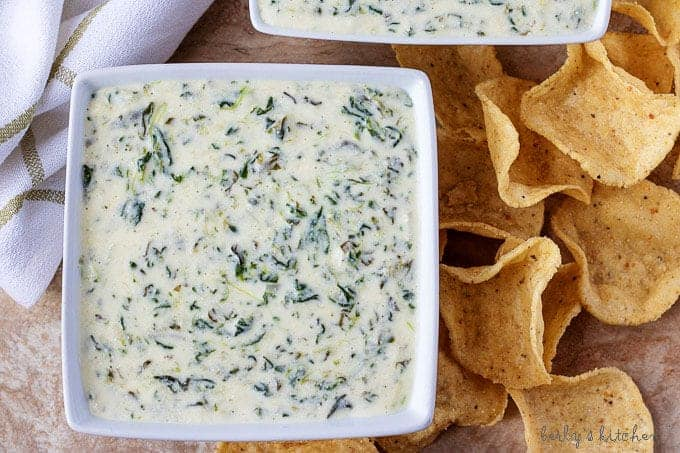 Ariel view of two square bowls of Instant Pot Hot Spinach Dip with tortilla chips