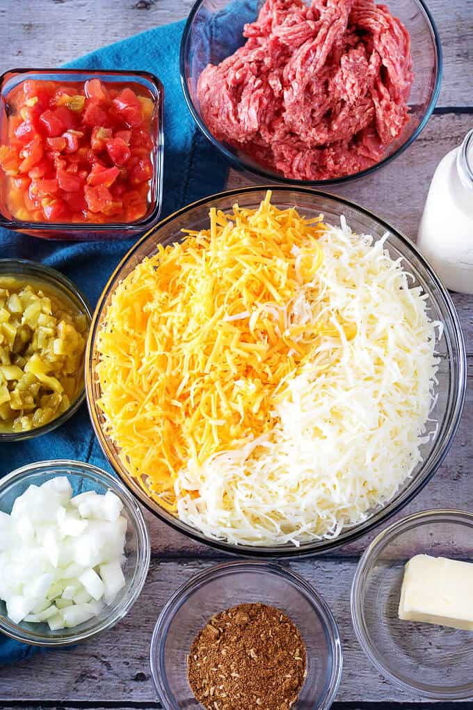 Ariel view of cheese, tomatoes, ground beef, taco seasoning, onions, and green chiles used in hamburger dip.