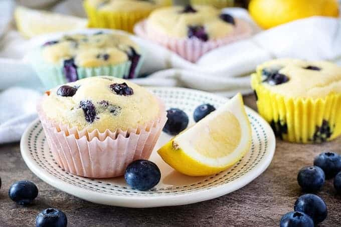 A close-up picture of the lemon blueberry muffins on plates in Spring themed cupcake liners.