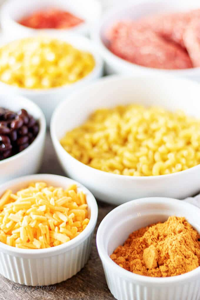 A photo of all the ingredients needed for taco pasta salad, like corn, taco seasoning, black beans, and cheese in white bowls.