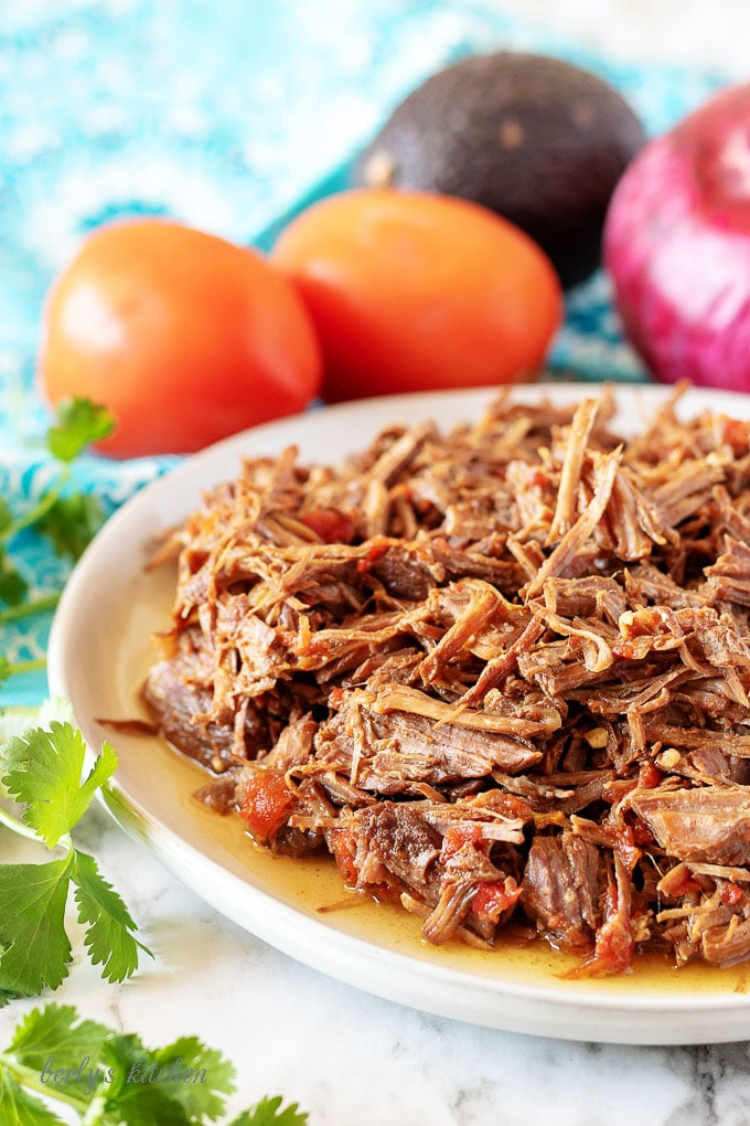 A plate of shredded beef and tomatoes used to fill shredded beef tacos.