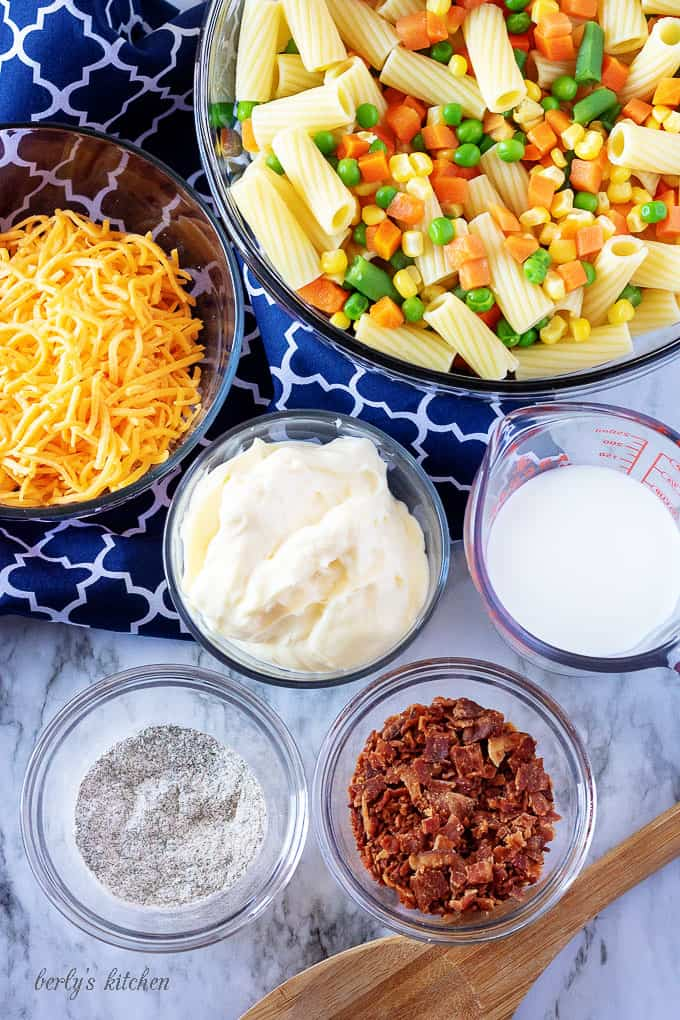 Multiple clear glass mixing bowls showing the ingredients needed for the cold pasta salad, like mayo, bacon, and shredded cheddar cheese.