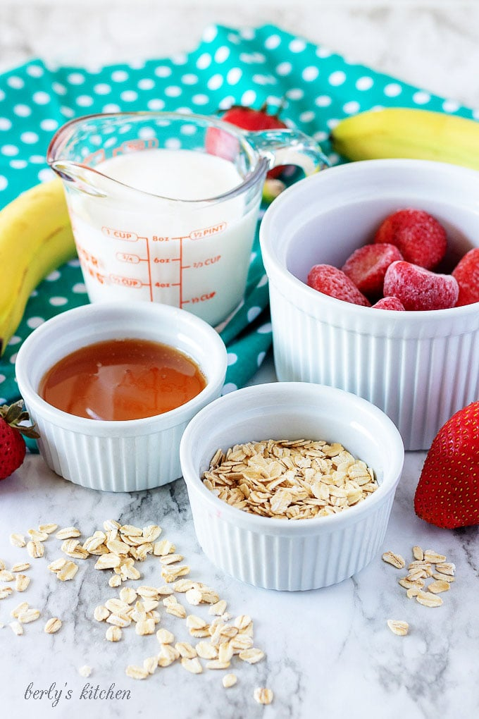 The strawberry banana smoothie ingredients like milk, honey, oats, and strawberries.