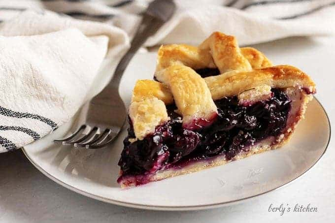 The finished blueberry pie recipe with a slice of pie sitting on a white plate.