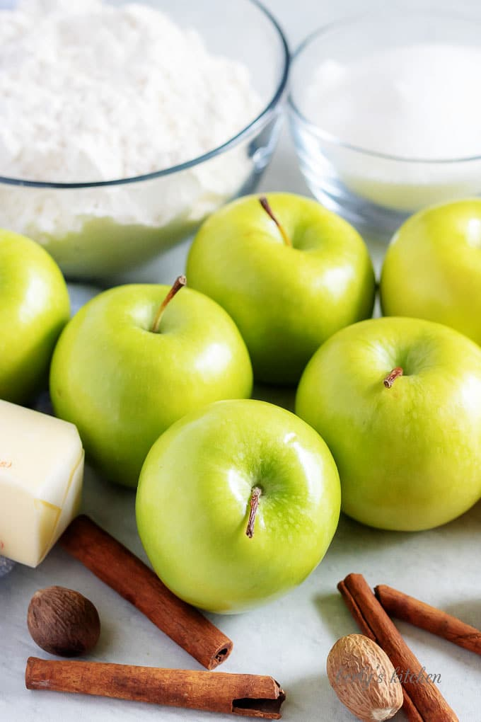 The Granny Smith apple pie ingredients like apples, cinnamon, and sugar.