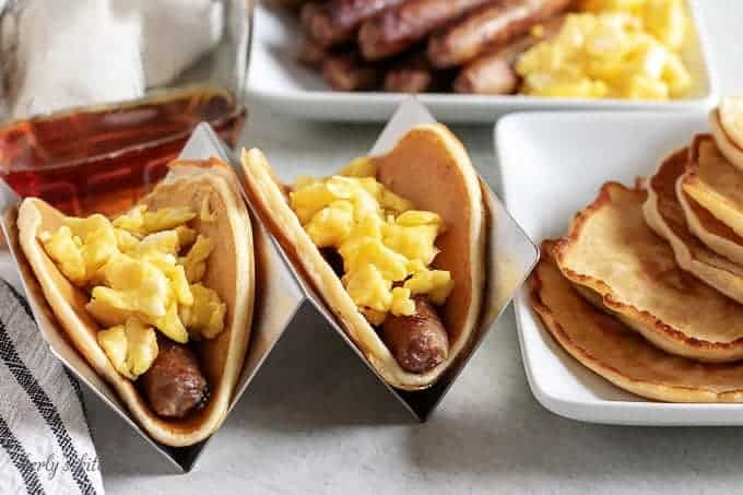 Two breakfast tacos in holders loaded with eggs, sausage, and syrup.
