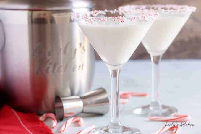 Two peppermint martinis in martini glasses, with a candy cane garnish.