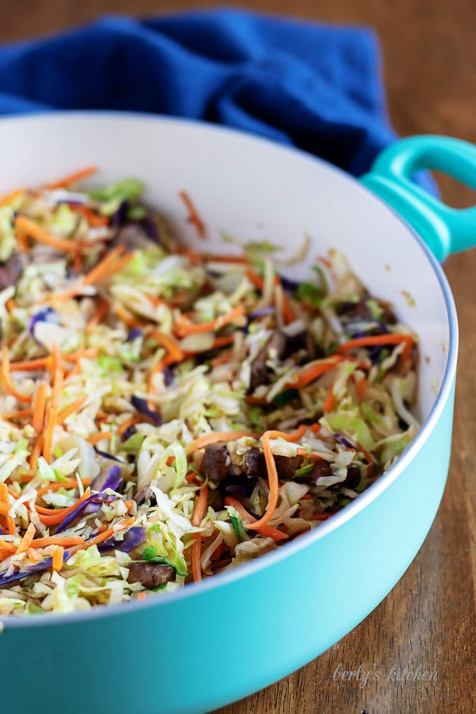 The carrots, mushrooms, and slaw, cooked in a large skillet.