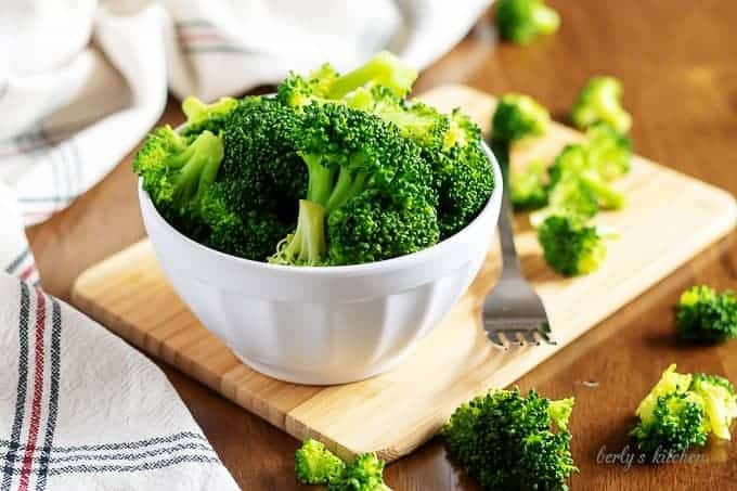The steamed broccoli in a small white bowl with a fork.
