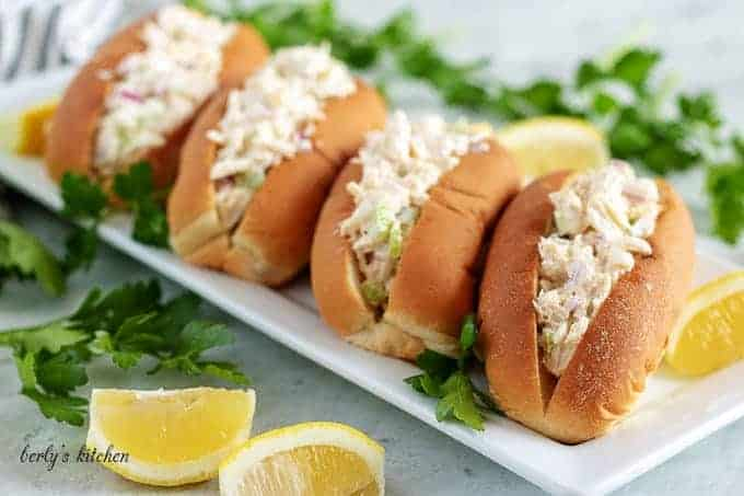 Four crab rolls, on a long rectangular plate, garnished with fresh parsley.