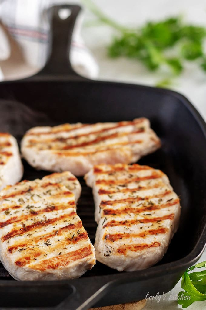 Four pork chops grilling in a cast iron griddle pan.