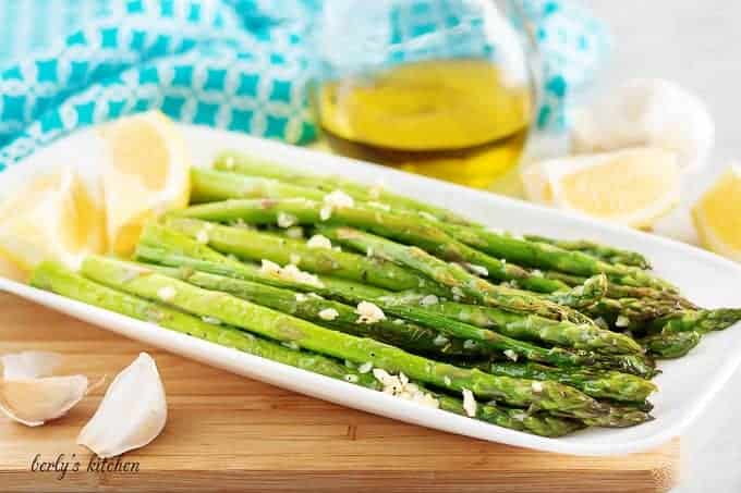 The sauteed asparagus, topped with garlic, sitting on a rectangular plate.