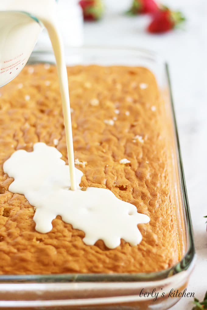 Pouring the sweet three milk mixture onto the cooled cake.