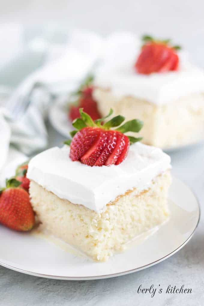 A slice of tres leches cake sitting on a white saucer.
