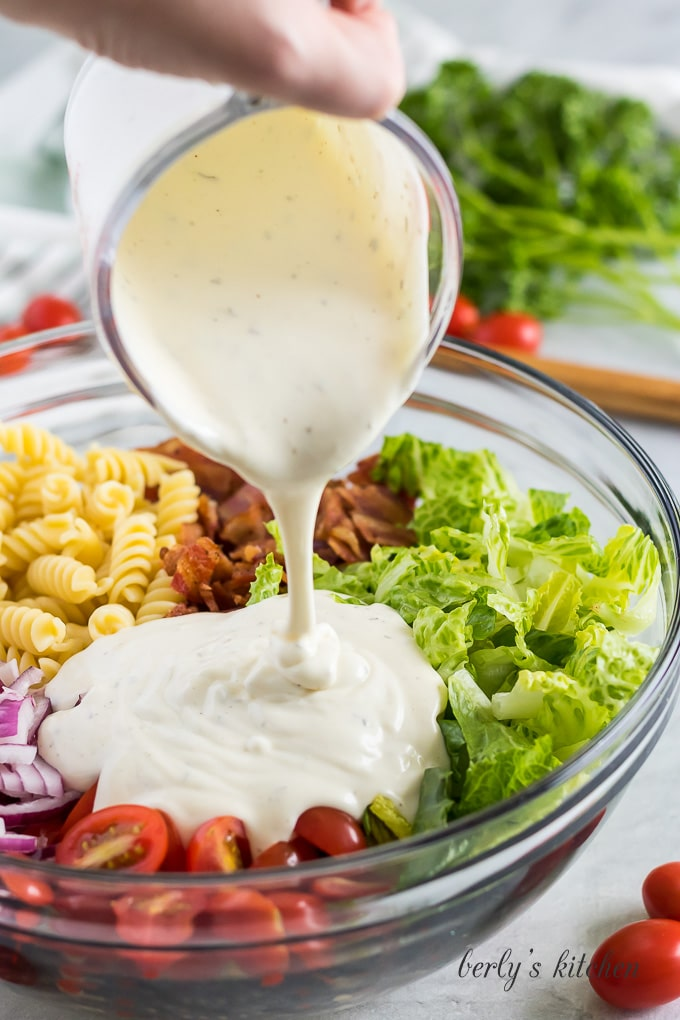 A measuring cup pouring ranch dressing over the other ingredients.
