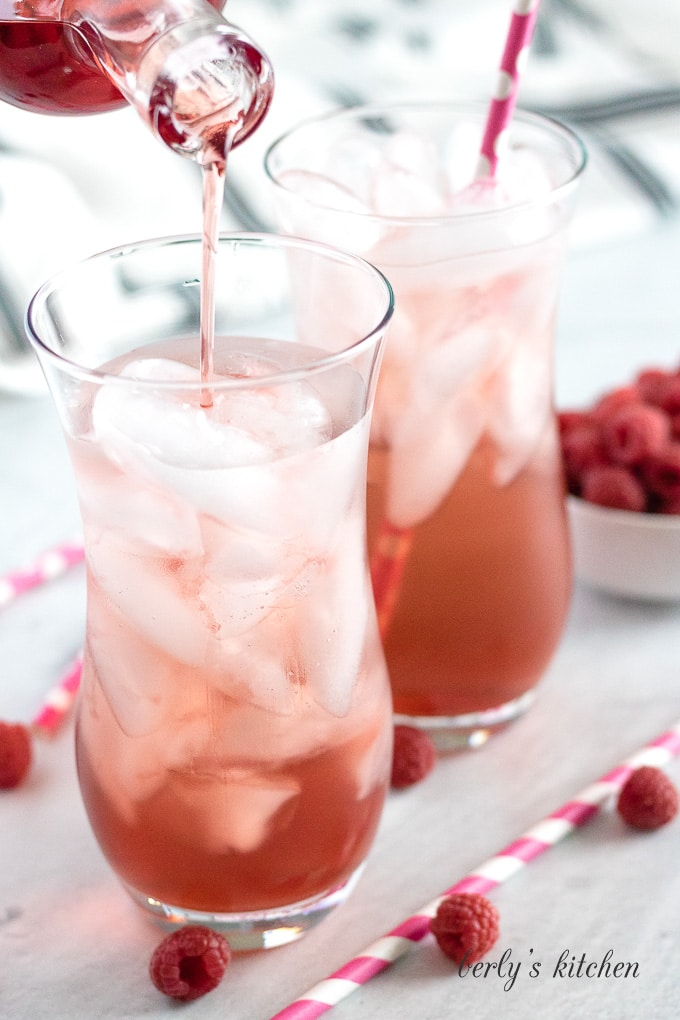 Raspberry syrup being poured into a glass with club soda and ice.