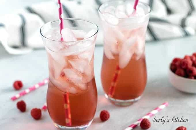 Two glasses of raspberry Italian soda served with ice and straws.