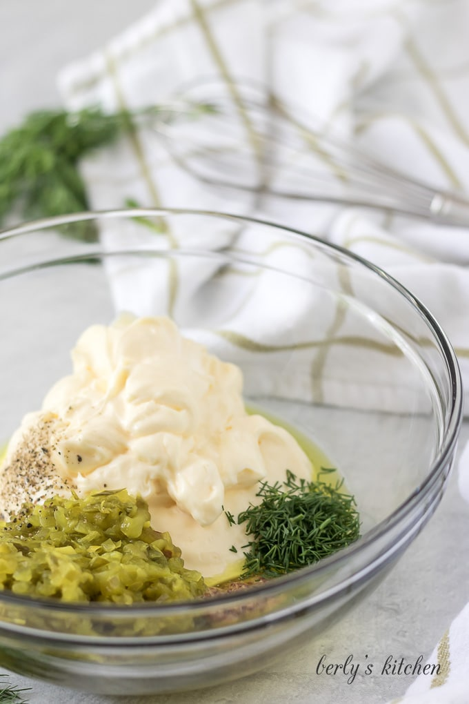 The mayo, dill, relish, and other ingredients in a mixing bowl.