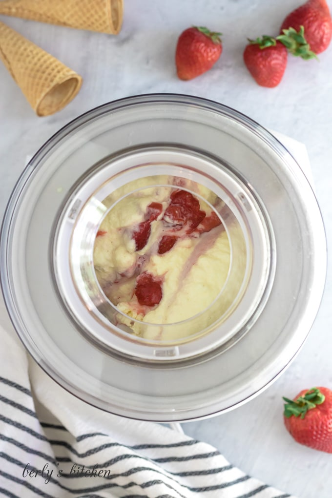 Strawberry puree and sauce added to the ice cream as it churns.