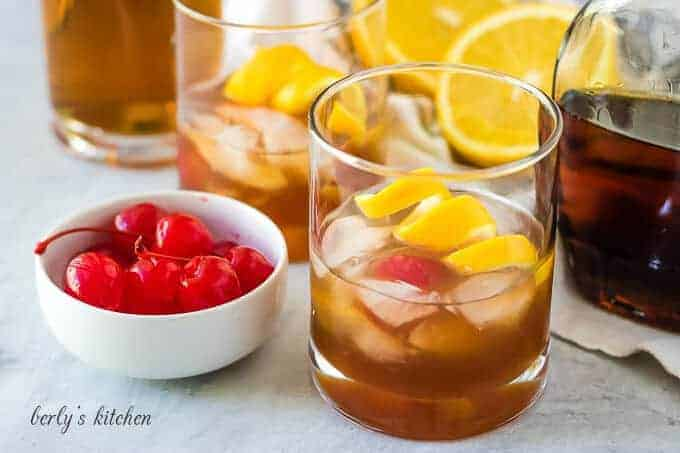 Two maple old fashioned cocktails beside a bowl of cherries.