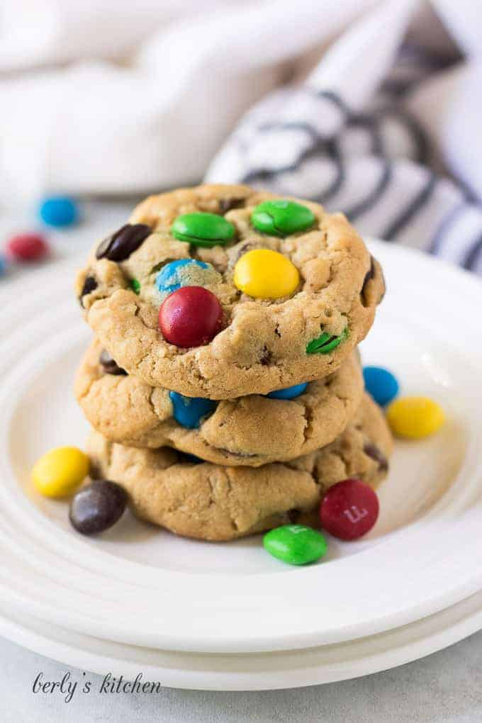 A stack of cookies on a white plate with candy.