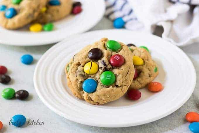 Two monster cookies on a plate with colorful chocolate candies.