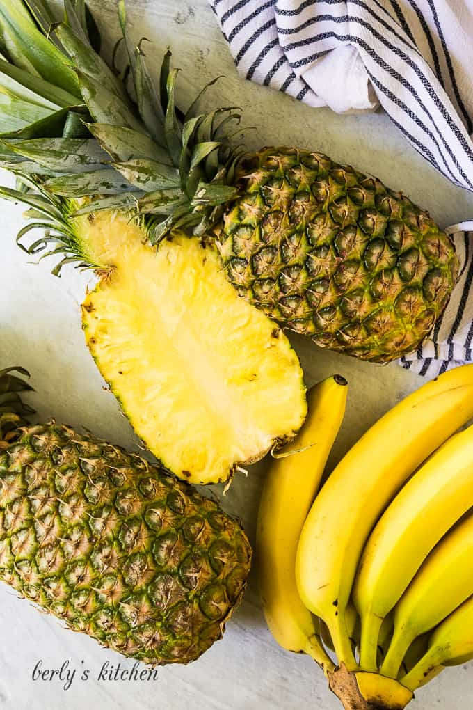 Fresh bananas and pineapples decoratively arranged on a marble table.