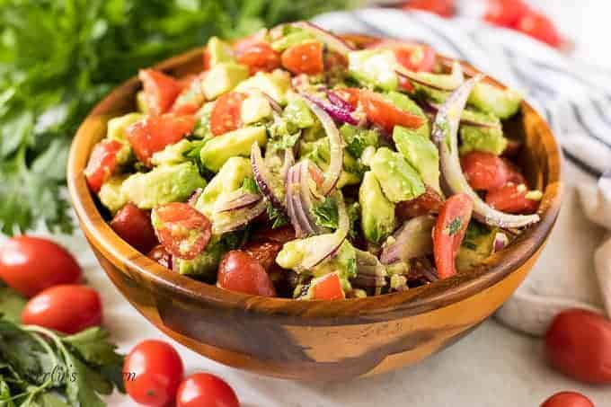 The tomato avocado salad in a wooden bowl.