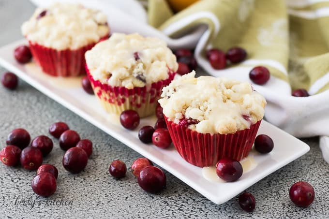 Three cranberry orange muffins on a plate topped with glaze.