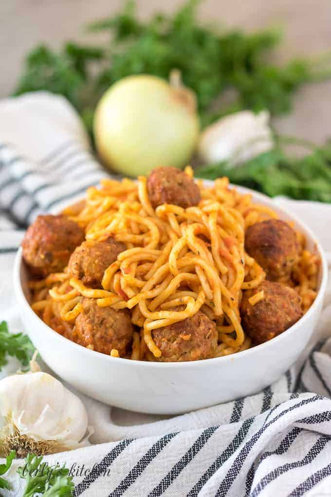 The spaghetti with meatballs served in a decorative white bowl.
