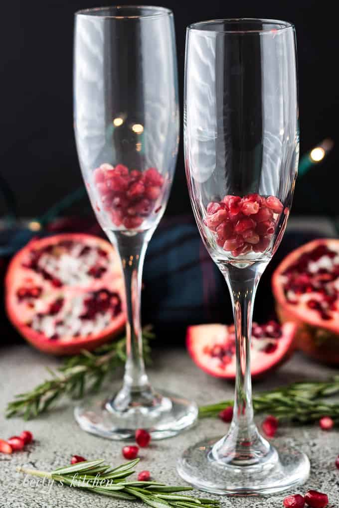 A handful of pomegranate seeds inside two tall champagne glasses.