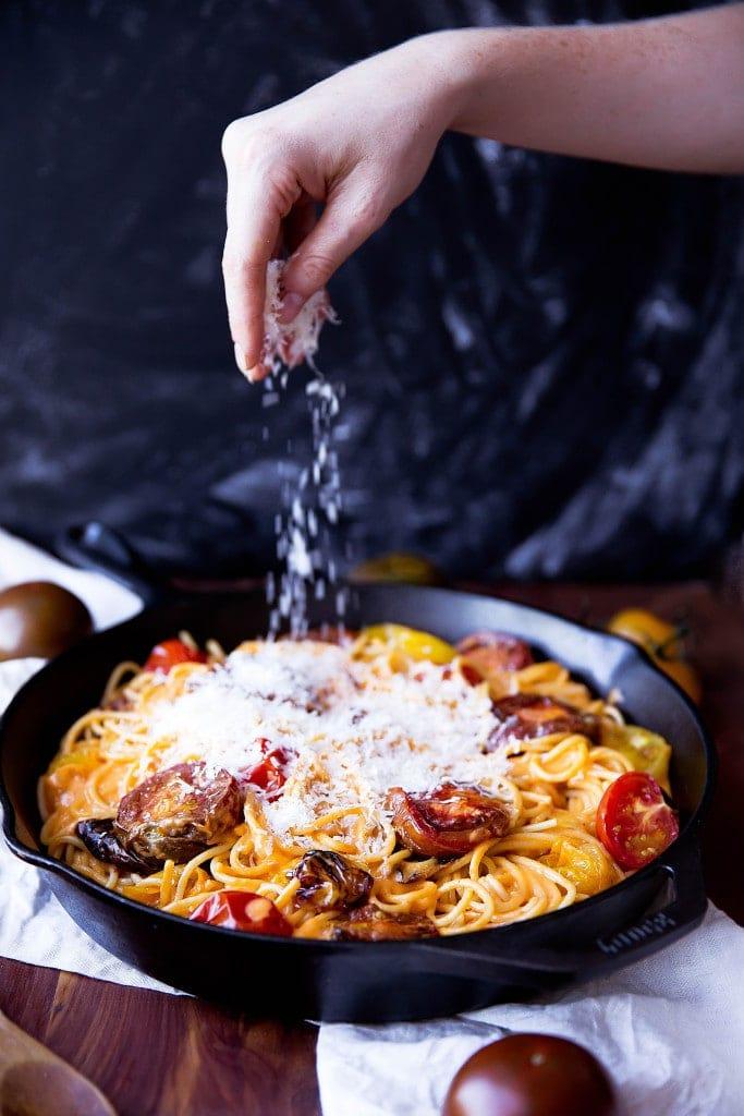 sprinkling parmesan onto spaghetti with tomato cream sauce