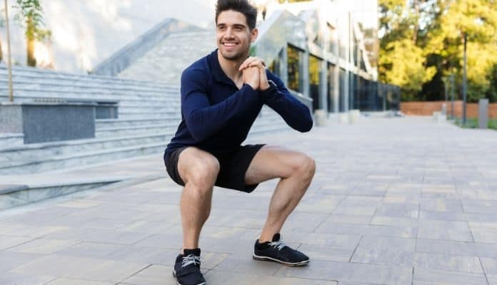 Man doing squat exercise to reduce delayed onset muscle soreness